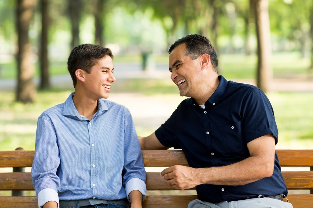 Hispanic father and son talking and laughing on a bench.