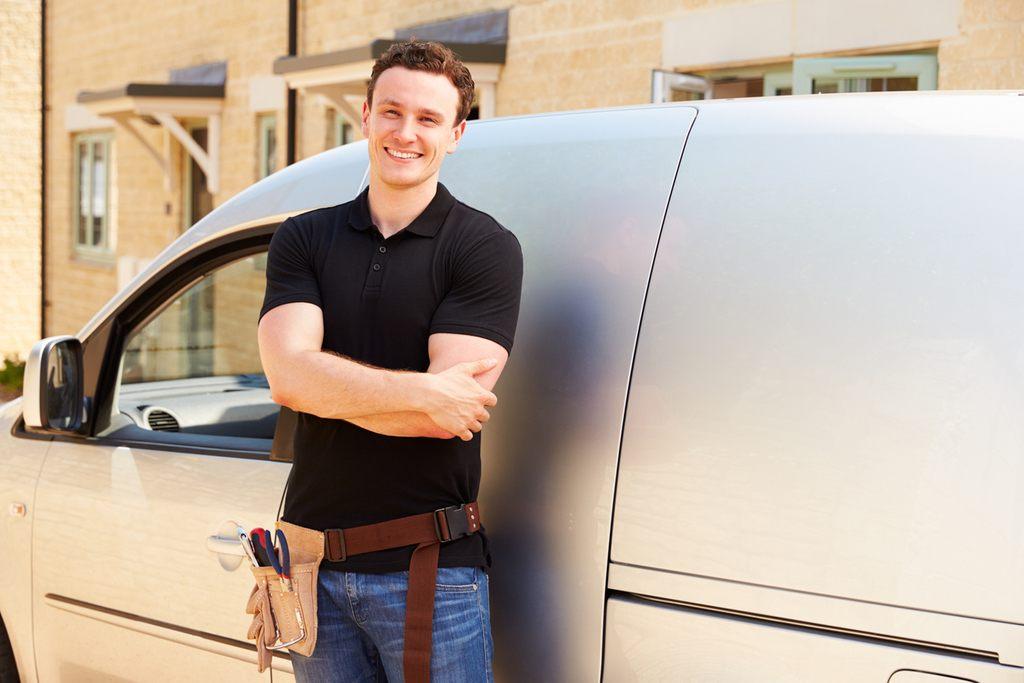 A happy tradesman standing by his van.
