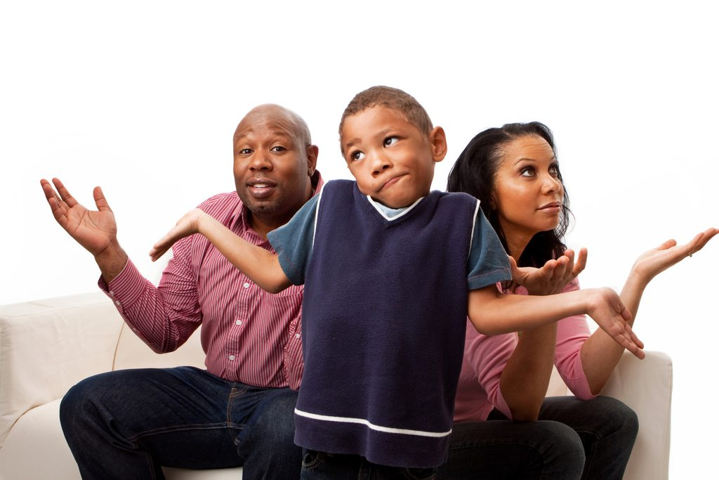 Black parents and boy gesturing with hands and faces that they are confused.