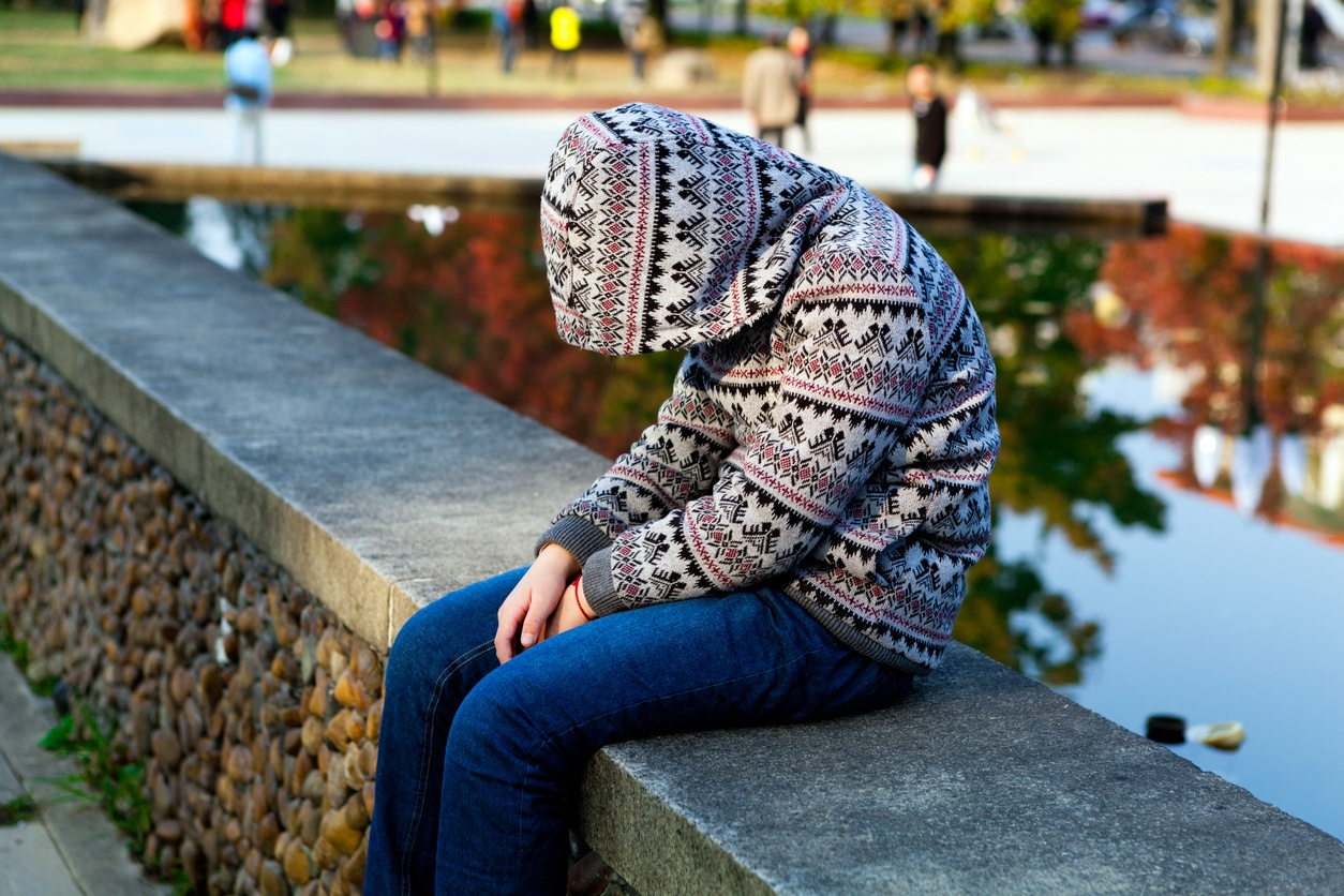 Depressed Child sitting sadly on a bench, head bowed.
