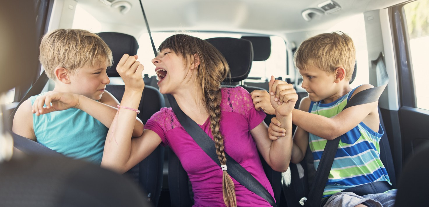 Three children fighting in a car.